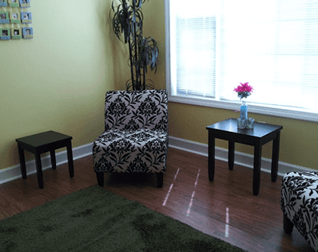 A photograph of our waiting room there are two chairs and a side table with a flower.