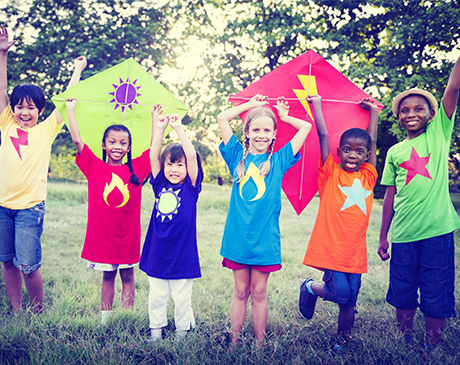 multi-cultural group of children, each with a different color shirt with kites